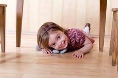 Happy little girl crawling on the hardwood floor stock images