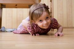 Happy little girl crawling on the hardwood floor Royalty Free Stock Images