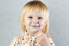 Happy  little girl  with cream on her face Royalty Free Stock Images