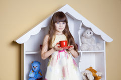 Happy little girl with cup of tea in her room. Stock Image