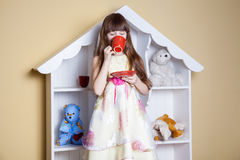 Happy little girl with cup of tea in her room. Royalty Free Stock Photos
