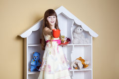 Happy little girl with cup of tea in her room. Stock Photos