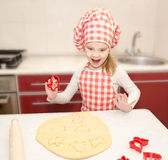Happy little girl cuts dough with form for cookies Royalty Free Stock Photos