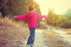 Happy little girl dancing on rural road royalty free stock image