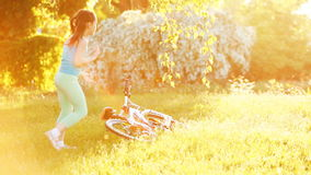 Happy little girl are dancing on the meadow at bright sunshiny day. stock footage