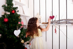 Happy  little girl decorate Christmas tree and home. Royalty Free Stock Photos