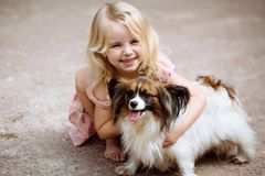 Happy little girl with a dog standing on the road in the park. Cute little girl hugging a dog, smiling. Child with dogs. Puppies and children outdoors royalty free stock image