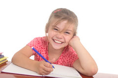 Happy little girl doing homework Stock Images