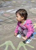 Happy little girl draw with chalk on the pavement Royalty Free Stock Photo