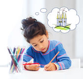Happy little girl drawing castle with crayons. People, childhood, creativity and imagination concept - happy little girl drawing with crayons and dreaming about Stock Photos