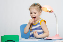Happy little girl drawing a pencil stuck in her mouth Stock Photography