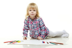 Happy little girl draws a picture. Royalty Free Stock Photography