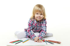 Happy little girl draws a picture. Royalty Free Stock Image