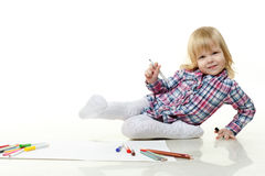 Happy little girl draws a picture. Royalty Free Stock Images