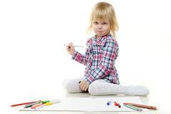 Happy little girl draws a picture. Stock Photo