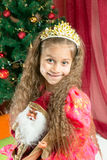 Happy little girl in a dress at Christmas. Happy little girl holding Christmas toy on the Christmas tree. Stock Images