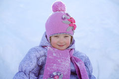 Happy little girl dressed in pink scarf sits on snow Royalty Free Stock Images