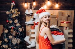 Happy little girl dressed in winter clothing think about Santa near Christmas tree. Teenager Christmas. Winter evening stock photo