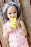Happy little girl drinking juice Stock Photography