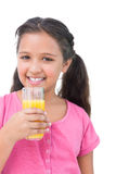 Happy little girl drinking orange juice Royalty Free Stock Photos