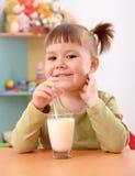 Happy little girl drinks milk. In preschool Stock Photos