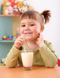 Happy little girl drinks milk Stock Photos