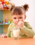 Happy little girl drinks milk. In preschool Royalty Free Stock Photo