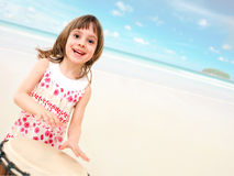 Happy little girl with drum on the beach Stock Image