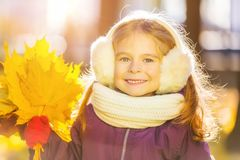 Happy little girl in earflaps with autumn leaves. In the park Stock Photography