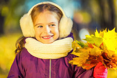 Happy little girl in earflaps with autumn leaves Royalty Free Stock Image