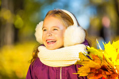 Happy little girl in earflaps with autumn leaves. In the park Stock Photos