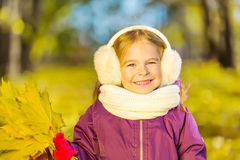 Happy little girl in earflaps with autumn leaves Royalty Free Stock Photos
