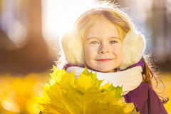 Happy little girl in earflaps with autumn leaves. In the park Stock Photo