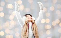 Happy little girl in earmuffs over holidays lights Stock Photo