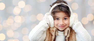 Happy little girl in earmuffs over holidays lights Stock Images