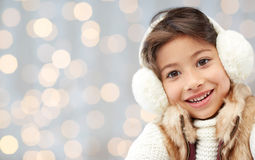 Happy little girl in earmuffs over holidays lights Royalty Free Stock Photo