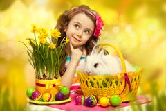Happy little girl with easter rabbit and eggs. Thoughtful little girl with easter rabbit in basket and eggs. Greeting card Royalty Free Stock Photos