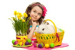 Happy little girl with easter rabbit and eggs. Thoughtful little girl with easter rabbit in basket and eggs. Greeting card. Isolated on white background Stock Photos