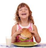 Happy little girl eat big sandwich Stock Photography