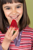 Happy little girl eating a big strawberry Stock Images