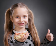 Happy little girl eating bread and butter with fish Stock Images