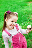 Happy little girl eating cake and having fun at the park Royalty Free Stock Photography