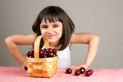 Happy little girl eating cherries Stock Photos