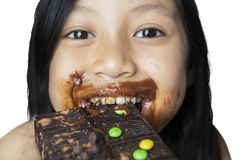 Happy little girl eating chocolate bar on studio. Closeup of a happy little girl eating chocolate bar while looking at the camera,  on white background Royalty Free Stock Photo