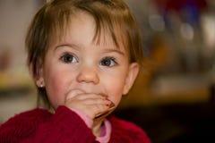 Happy little girl eating chocolate Stock Image