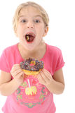Happy little girl eating chocolate doughnut Stock Photos