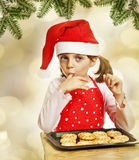 Happy little girl eating Christmas cookies Royalty Free Stock Images