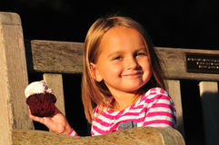 Happy little girl eating a cupcake royalty free stock photography