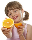 Happy little girl eating fresh orange Stock Images