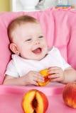 Happy little girl eating fruit Stock Images